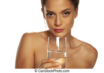 Young beautiful woman holding glass with water on white background