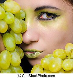 Young beautiful woman holding green grapes closeup