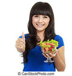 Young beautiful woman holding huge glass of fruits and showing thumbs up over white background