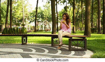 Young beautiful woman holding mobile phone and sitting on bench in summer park