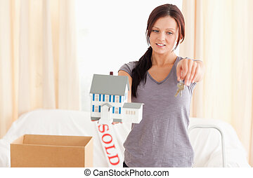 Young beautiful woman holding model house and keys