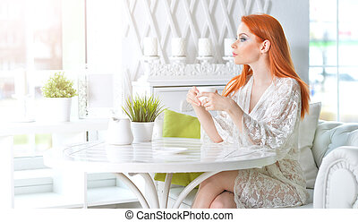 Young beautiful woman holding white cup at home
