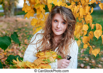 young beautiful woman holding yellow leaves