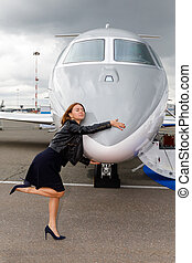 young beautiful woman hugs the nose of the the business jet