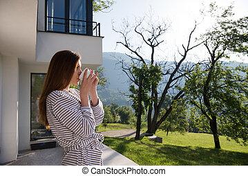woman in a bathrobe enjoying morning coffee