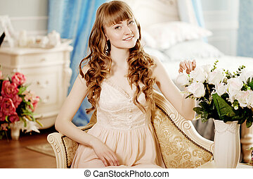 Young beautiful woman in a bedroom