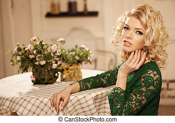 Young beautiful woman in a cafe. Modern trendy blondy girl...
