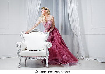 Young beautiful woman in a luxurious pink dress, in interior near the white chairs