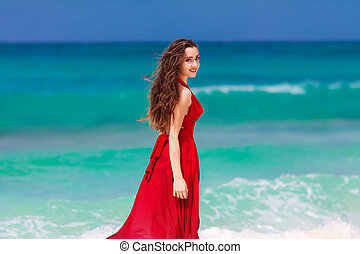 young beautiful woman in a red dress  standing on the tropical sea coast