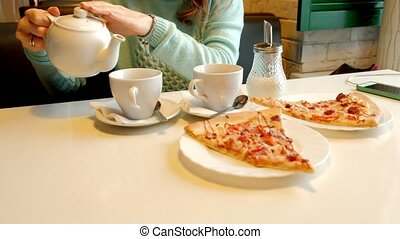 Young beautiful woman in a restaurant eating pizza and drinking tea