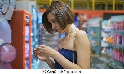 Young, beautiful woman in a supermarket chooses cosmetics.