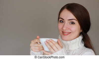 Young beautiful woman in a warm winter sweater drinks a hot...