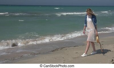 young beautiful woman in a white transparent dress and denim jacket walking along the seashore