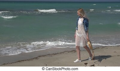 young beautiful woman in a white transparent dress with white hair flying in the wind walks along the seashore and smiles