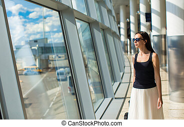 Young beautiful woman in airport while waiting for flight