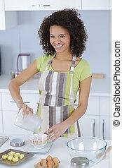 young beautiful woman in an apron making cake