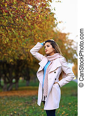 Young beautiful woman in autumn park posing