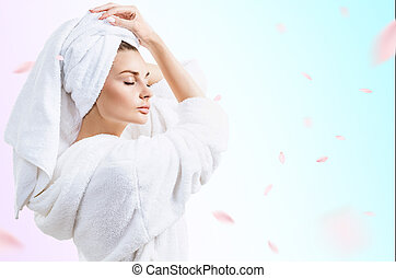 Young beautiful woman in bathrobe over fresh blue background.