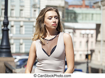 Young beautiful woman in beige short dress posing outdoors in sunny weather