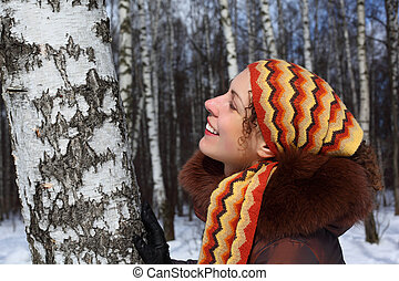 Young beautiful woman in birch wood in winter