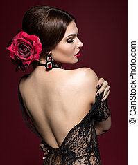 Young beautiful woman in black dress and black rose flower...