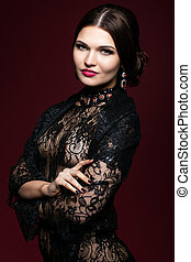 Young beautiful woman in black dress on marsala color background