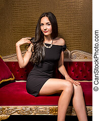 Young beautiful woman in black little dress sitting on a red velvet sofa