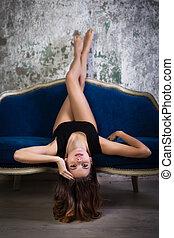 Young beautiful woman in black underwear on sofa