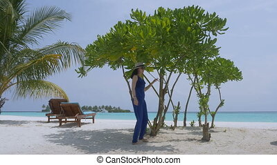 Young beautiful woman in blue jumpsuit on tropical beach,...