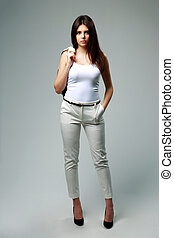 Young beautiful woman in casual clothes standing on gray background