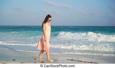 Young beautiful woman in dress on the seashore on sunset