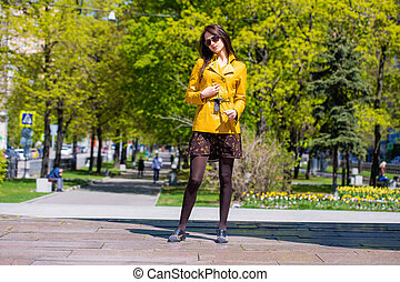 Young beautiful woman in golden jacket