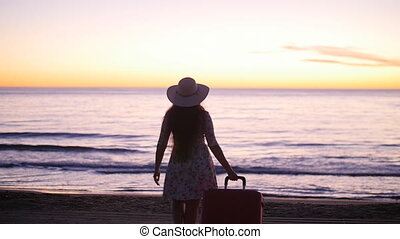 Young beautiful woman in hat with large suitcase on beach