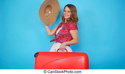 Young beautiful woman in hat with suitcase