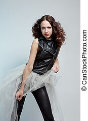 Young beautiful woman in leather jacket and tutu