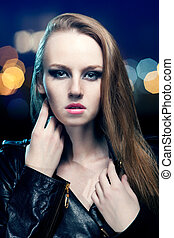 Young beautiful woman in leather jacket on background of night l