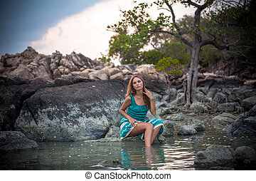 Young beautiful woman in long turquoise dress sitting on a stone by the sea