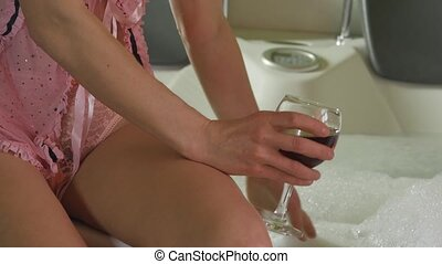 Young beautiful woman in pink panties and bra in a bathroom with glass of wine in her hand