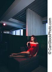 Young beautiful woman in red dress, reclining on a green background