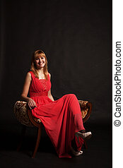 young beautiful woman in red dress sitting on a chair