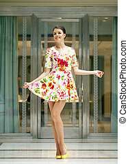 Young beautiful woman in red flowers dress