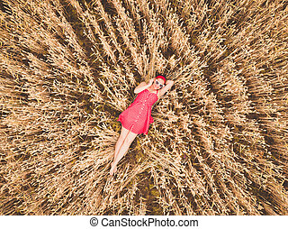 Young beautiful woman in red retro dress and sunglasses lying in wheat yellow field. Flying close above cornfield. AERIAL Drone view. Harvest, agriculture concept.