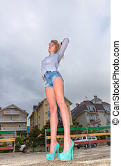 Young beautiful woman in shorts urban style