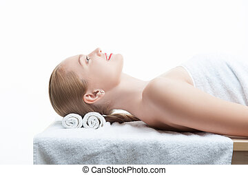 Young beautiful woman in spa relaxing on massage table -...
