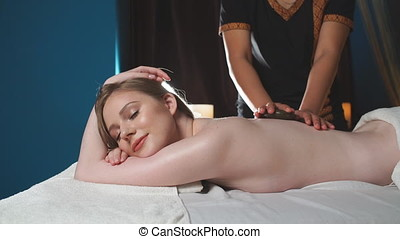 Young, beautiful woman in spa salon lying on the coach...