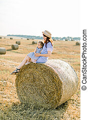 Young beautiful woman in striped dress and straw hat sits on hay bale and hugs her adorable little baby girl, enjoying summer sunset in field with haystacks
