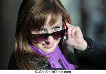 Young beautiful woman in sunglasses with phone