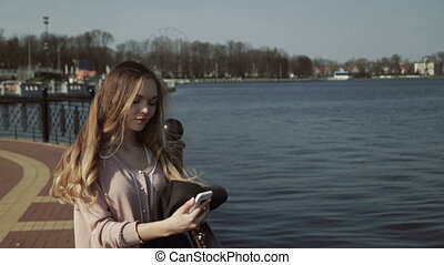 Young beautiful woman in the city park near the lake