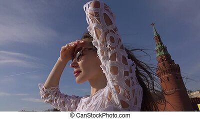 Young beautiful woman in white dress standing on the deck of boat passing Moscow Kremlin. 4K video