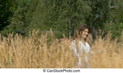 Young beautiful woman in white dress running across the field with wheat.